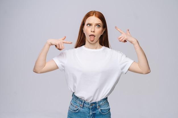 Сумасшедшая счастливая молодая женщина в футболке и джинсовых штанах показывает язык на изолированном белом фоне