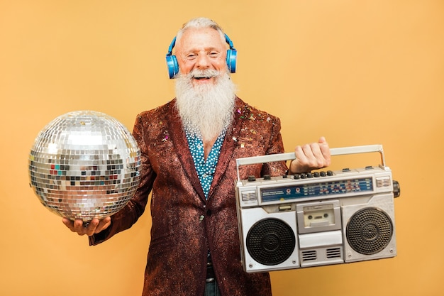 Crazy hipster man listening music with headphones while holding disco ball and vintage stereo - party concept