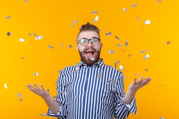 모자와 안경에 미친 즐거운 쾌활한 젊은 남자가 노란색 벽에 엄지 손가락을 보여줍니다. 성공적인 파티와 휴가의 개념. 광고 공간