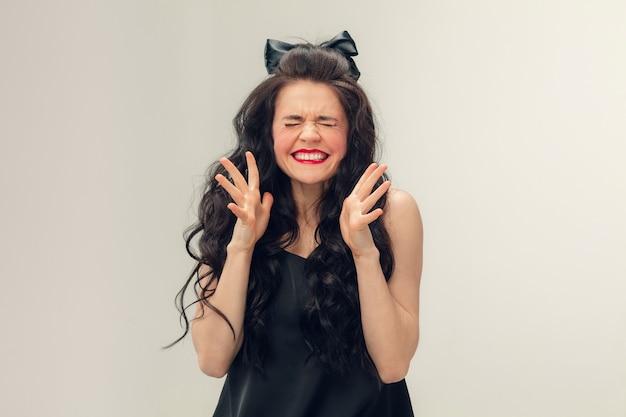 Безумный смех. портрет красивой молодой женщины на серой стене. кавказская милая брюнетка женская модель с длинными вьющимися волосами. понятие красоты, моды, косметики. copyspace для рекламы.