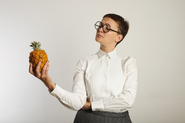 Сумасшедший учитель в консервативной одежде, вопросительно смотрит на ананас, изолированный на белом