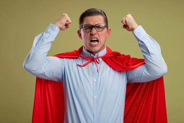 赤いマントとメガネでクレイジーな狂気と怒りのスーパーヒーローのビジネスマンは、明るい背景の上に立っている上げられたくいしばられた握りこぶしで攻撃的な表情で叫んでいます