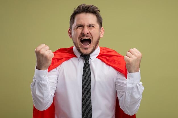 Сумасшедший, безумный и злой супергерой, бизнесмен в красной накидке, сжимающий кулаки с агрессивным выражением лица, сходит с ума и кричит, стоя над зеленой стеной