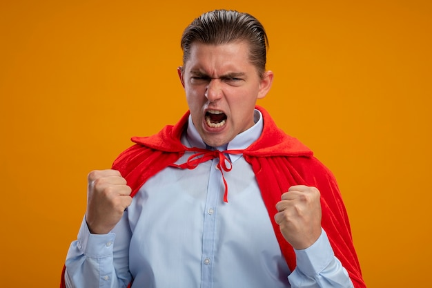 Crazy mad and angry super hero businessman in red cape clenching fists with agressive expression going wild shouting standing over orange background