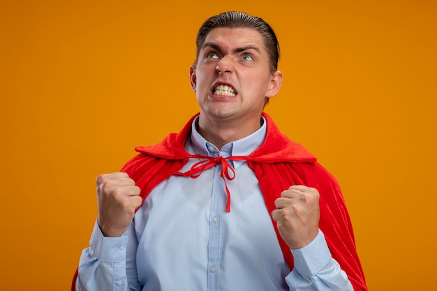 Crazy mad and angry super hero businessman in red cape clenching fists with agressive expression going wild standing over orange background