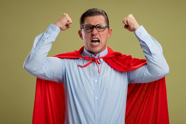 Crazy mad and angry super hero businessman in red cape and glasses shouting with aggressive expression with raised clenched fists standing over light background
