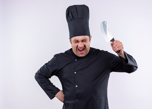 黒の制服を着て、白い背景の上に立っている怒っている顔で叫んでナイフを振る料理人の狂った男性シェフの料理人