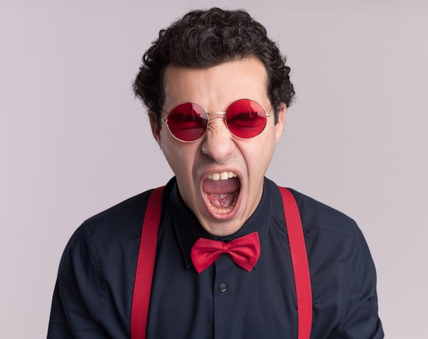 白い壁の上に立って攻撃的な表情で叫んで眼鏡とサスペンダーを身に着けている蝶ネクタイと狂気の狂ったスタイリッシュな男