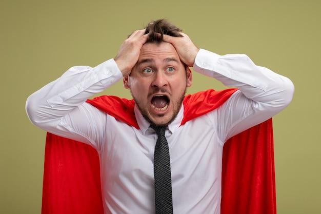 Uomo d'affari pazzo super eroe pazzo in mantello rosso che grida con espressione aggressiva tirando i capelli che si scatenano in piedi sopra la parete verde