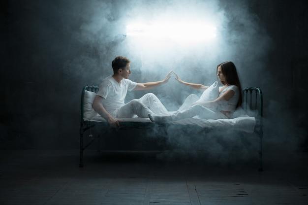 Сумасшедшие мужчина и женщина сидят в постели, бессонница, темная комната .. психоделики имеют проблемы каждую ночь, депрессия и стресс, грусть, психиатрическая больница.