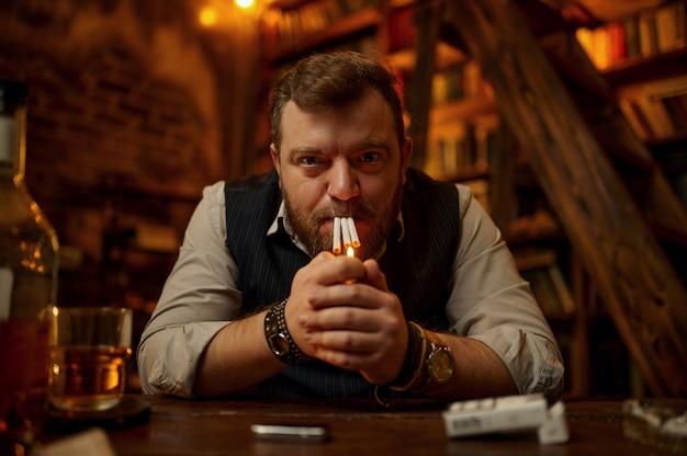 Сумасшедший человек курит три сигареты одновременно, винтажный офисный интерьер. культура табакокурения. вредная привычка и зависимость