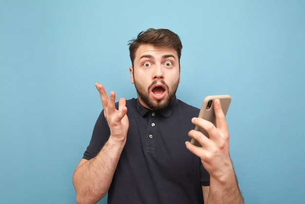 Crazy man wearing a beard wearing a dark t-shirt, standing on blue with a smartphone in his hands