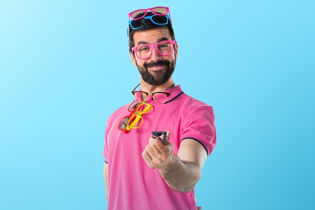 Crazy man with meny glasses on colorful background