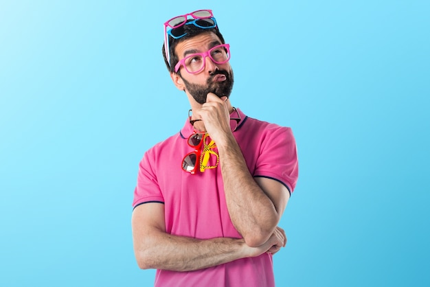 Crazy man with meny glasses thinking on colorful background