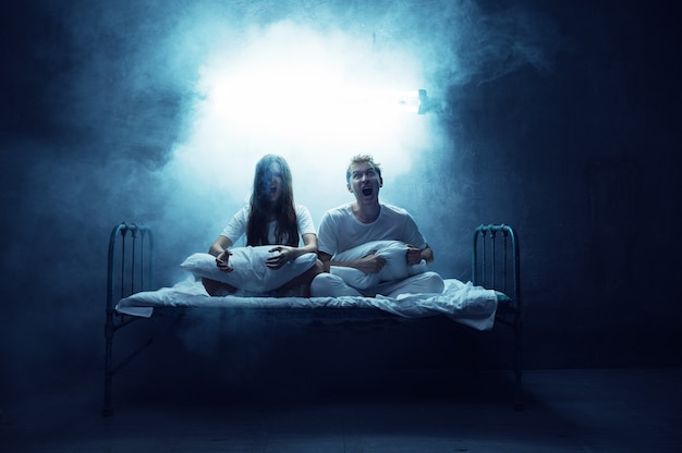 Crazy man and woman are screams in bed, insomnia horror, dark room . psychedelic having problems every night, depression and stress, sadness, psychiatry hospital