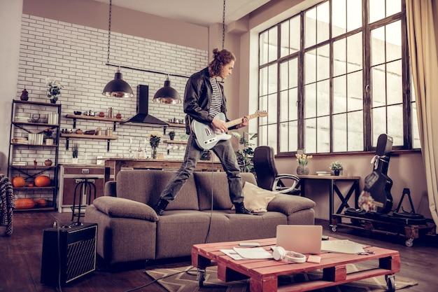 クレイジーミュージシャン。ソファに立って音楽を演奏しながらインスピレーションを得たクレイジーな若いロックミュージシャンの気持ち