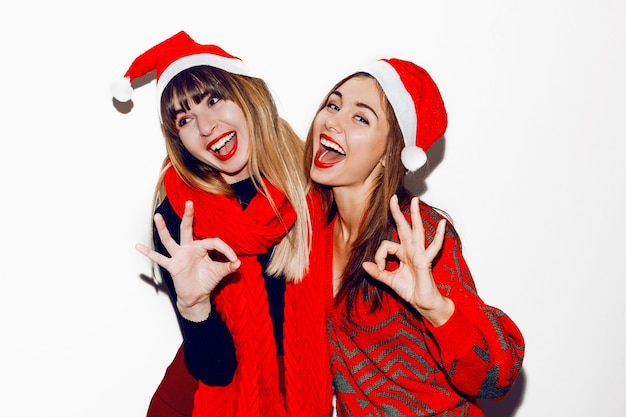 Crazy new year party mood. two drunk laughing women having fun and posing in cute masquerade hats. red sweater and scarf. showing ok by hands.