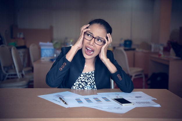 Сумасшедший офисный работник женщина сидит за столом. Premium Фотографии