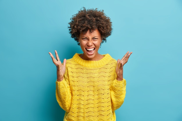 Crazy outraged curly haired woman screams loudly and gestures angrily yells furiously dressed in yellow knitted sweater poses against blue wall