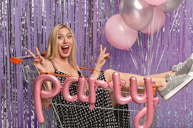 Crazy overjoyed blonde woman poses in shopping trolley, has fun on party celebration, makes peace sign with both hands, wears dress and sportshoes, poses against decorated tinsel curtain with balloons