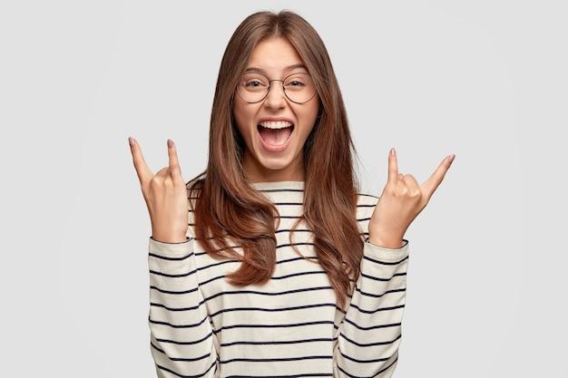 미친 기뻐하는 여자는 로큰롤 제스처를 만들고 투명한 안경, 줄무늬 스웨터, 흰 벽에 모델을 착용합니다. 혼자 실내 여성 로커 제스처를 웃 고. 경적 제스처 개념