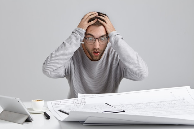 Crazy overworked architect has deadline, keeps hands on head, being in panic