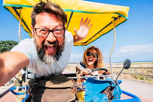 クレイジーな人々の幸せなカップルは、一緒に自転車を運転して休暇を楽しんでいます-夏休みを楽しんでいる大人の男性と女性のための観光客と幸せ。海とビーチ-女性に焦点を当てる