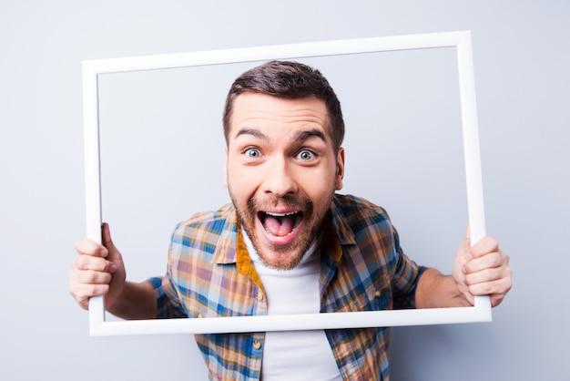 Безумная картина. красивый молодой человек в рубашке держит рамку перед его лицом и улыбается, стоя на сером фоне