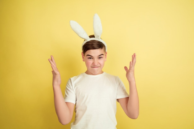 Crazy pointing up. caucasian boy as an easter bunny on yellow studio background. happy easter greetings. beautiful male model. concept of human emotions, facial expression, holidays. copyspace.