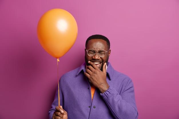 미친 긍정적 인 남자는 행복한 감정에서 웃고, 즐거운 시간을 보내고, 밝은 풍선으로 포즈를 취하고, 턱을 잡고, 보라색 재킷을 입습니다.