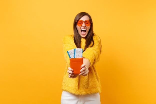 オレンジ色のハートのメガネで目を閉じて叫んで、黄色の背景で隔離のパスポート搭乗券のチケットを保持しているクレイジーなかなり若い女性。人々は誠実な感情、ライフスタイル。広告エリア。 Premium写真
