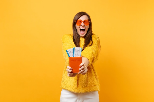 Crazy pretty young woman with closed eyes in orange heart glasses screaming, holding passport boarding pass tickets isolated on yellow background. people sincere emotions, lifestyle. advertising area.