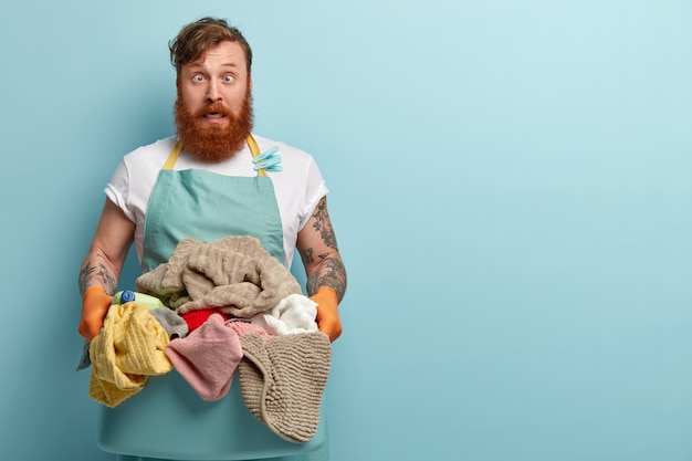 Crazy redhead man foolishes indoor, crosses eyes, wears casual apron and rubber gloves