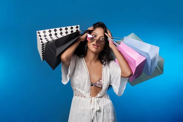 Сумасшедшая распродажа растрепанной межрасовой красивой девушки в белом платье в очках