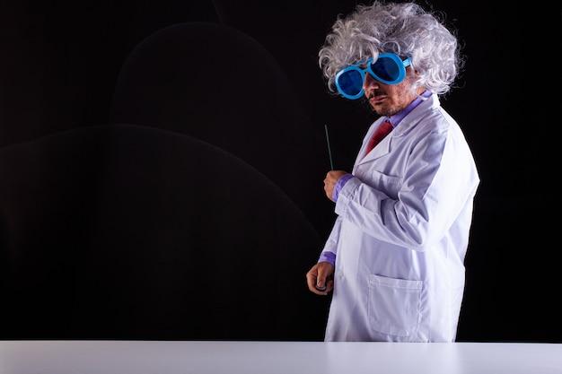 Сумасшедший учитель естествознания в белом халате с взлохмаченными волосами, в забавных очках держит палочку, чтобы указать на доску