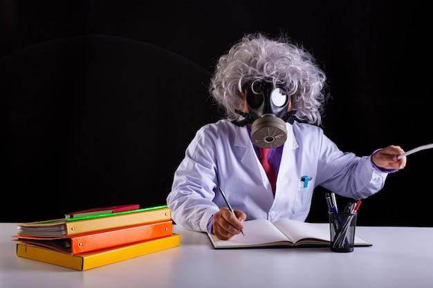 Сумасшедший учитель естественных наук в белом халате с растрепанными волосами сидит за столом в противогазе