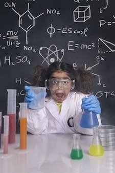 Crazy scientist girl with chemical flasks