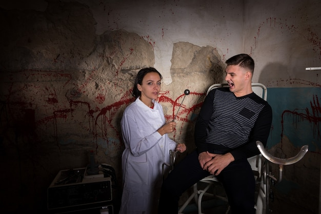 Crazy scientist holding iron medical device in front of screaming patient in dungeon with bloody walls in a halloween horror concept