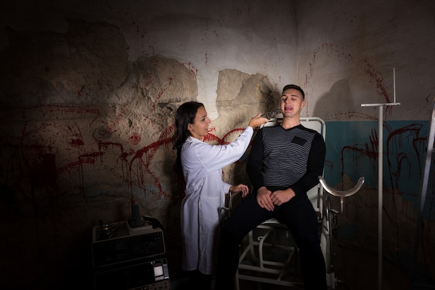 Crazy scientist holding medical forceps in front of patient in dungeon with bloody walls in a halloween horror concept