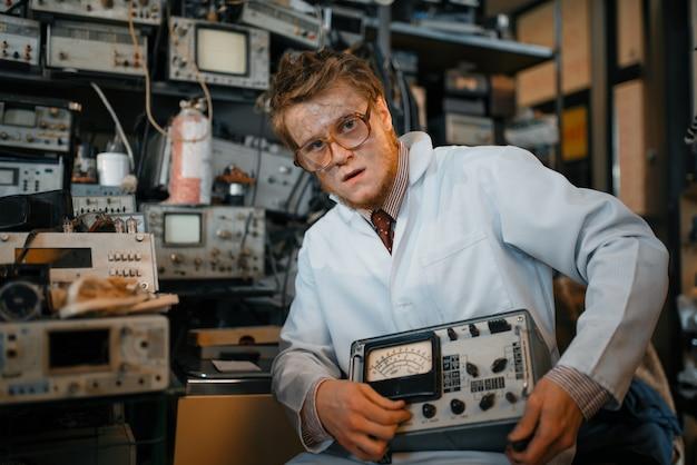 Сумасшедший ученый держит электрическое устройство в лаборатории