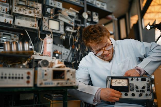 狂気の科学者は実験室で電気機器を保持しています。