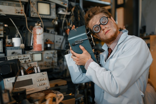 Сумасшедший ученый в очках держит электрическое устройство в лаборатории.
