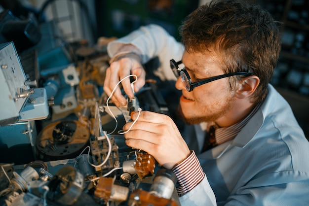 Сумасшедший ученый прототипирует электрическое устройство в лаборатории.