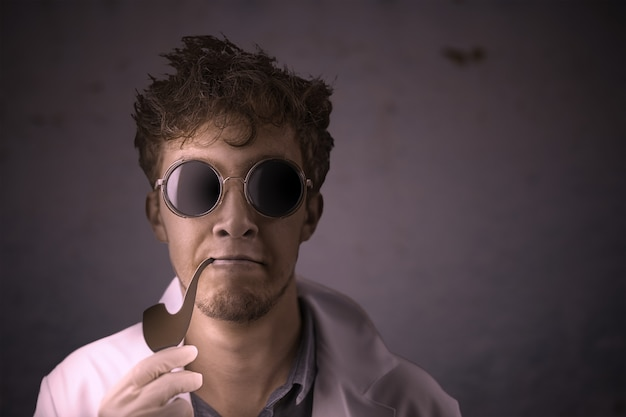 Crazy scientist with a smoking pipe in a coat and sunglasses on a dark old wall background