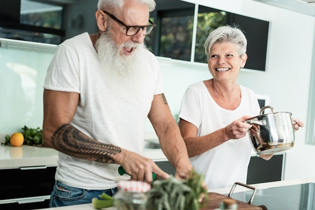Crazy senior couple cooking together at home