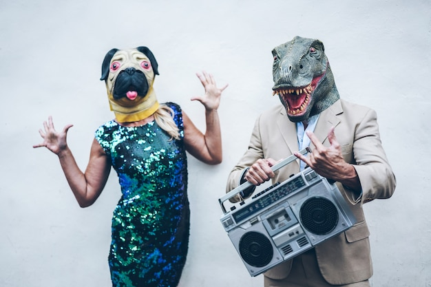 Crazy senior couple dancing for party wearing t-rex and chicken mask - old trendy people having fun listening music with boombox stereo