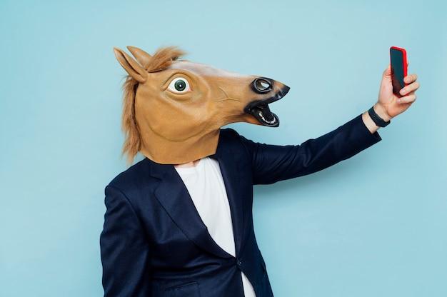 馬マスクを着用し、モバイルスマートフォンで自分撮りをしているクレイジーな年配の男性