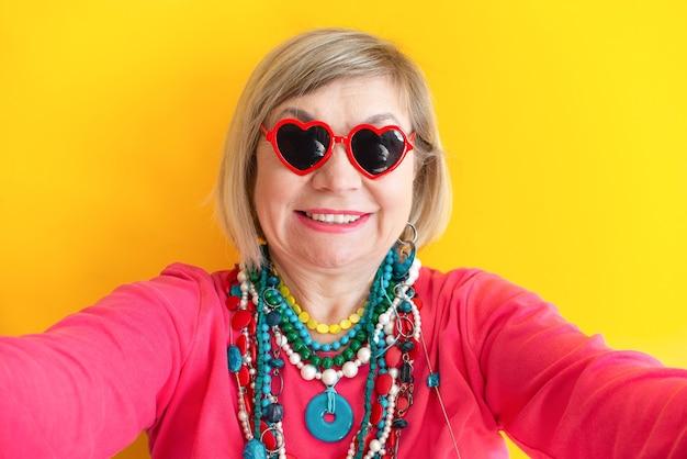세련된 옷을 입은 미친 고위 여성 연금 셀카 색 배경을 복용하는 행복한 할머니