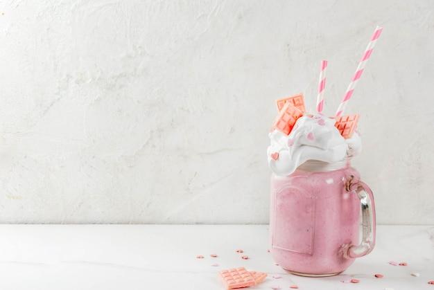 Безумный коктейль, романтический молочный коктейль на день святого валентина с сердечками из клубники, белого шоколада и леденцов, на белом фоне, copyspace