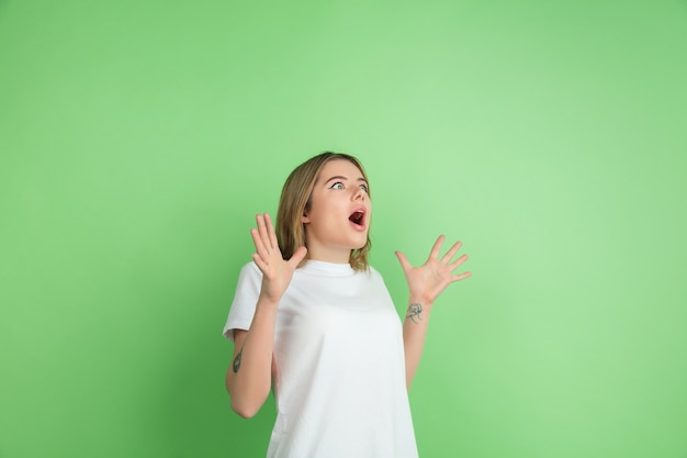 Crazy shocked. caucasian young woman's portrait isolated on green studio wall.
